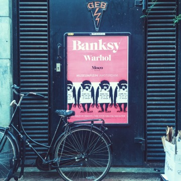 a poster of Banksy/Warhol exhibit